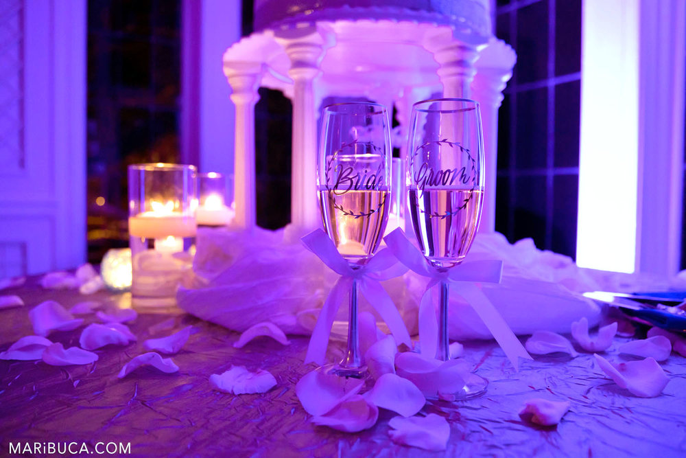 """Bride's and groom's champagne glasses with names on it """"bride"""" and """"groom"""" surrounded by lit candles and purple lights theme in the Morning Room, Kohl Mansion, Burlingame"""