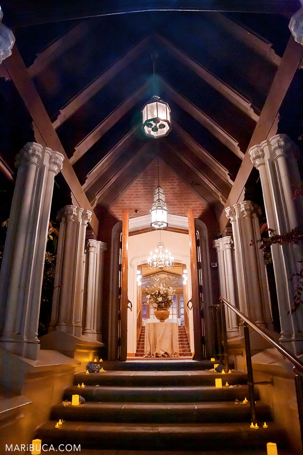 View from outdoor to Entry Hall, Kohl Mansion, Burlingame with high arch wooden columns and stands lit candles on the stairs.