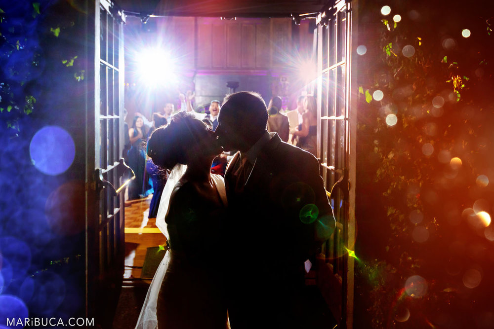 the bride and groom kiss as the last call that the wedding day ended on a background of dancing guests, and blue-and-orange light effects in the outdoor Great Hall, Kohl Mansion, Burlingame