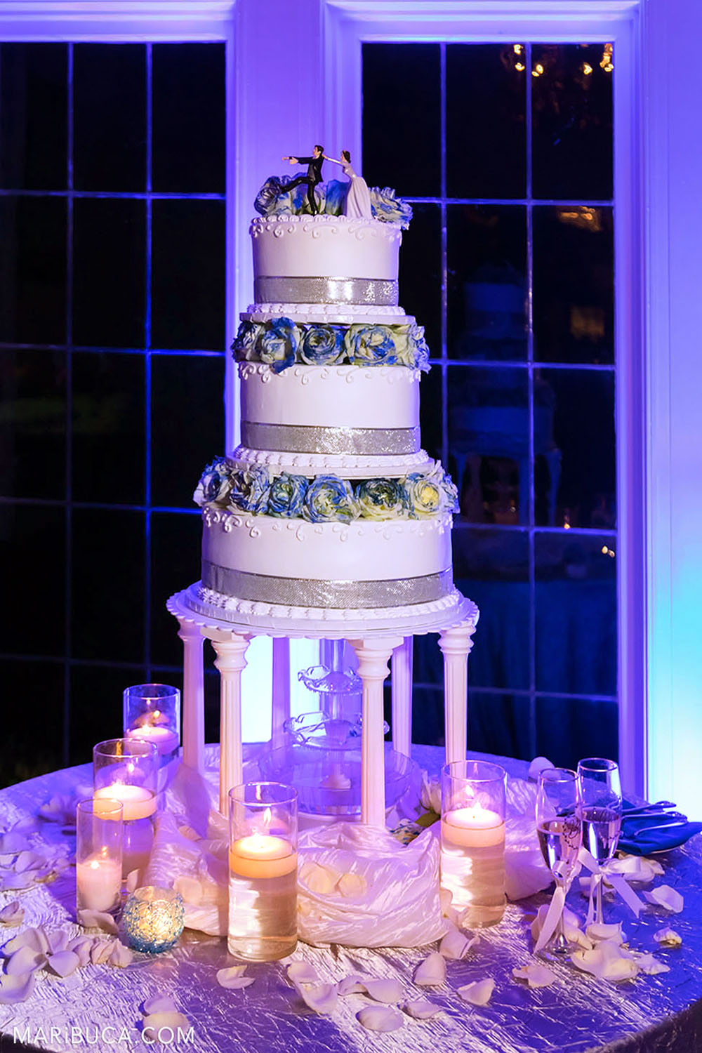 A three-story white cake with blue roses stands surrounded by lit candles on the water and purple light.