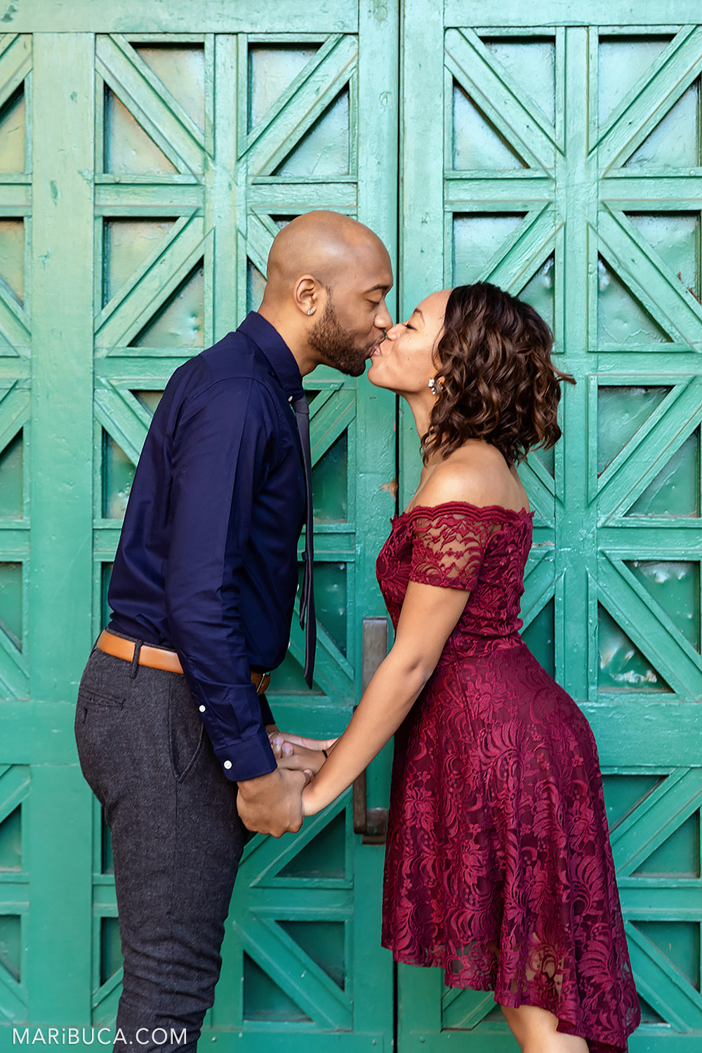 Fiance and fiancee are kissing each other in front of huge green gate in the San Francisco Engagement Palace of Fine Art