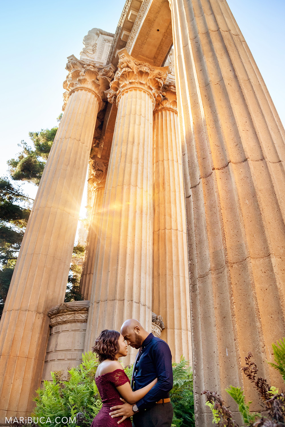 Adorable couple stand forehead to forehead and looking each other in the orange rays of sun in the San Francisco Engagement Palace of Fine Art