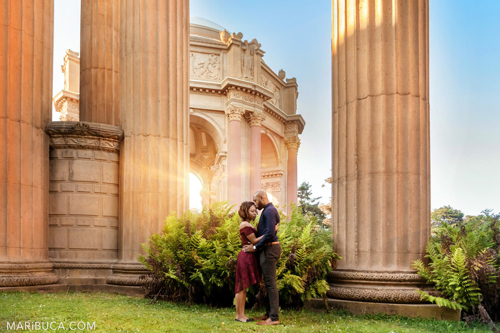 In the engagement photo session the couple are hugging each other in the orange beautiful background in the San Francisco Palace of Fine Art.