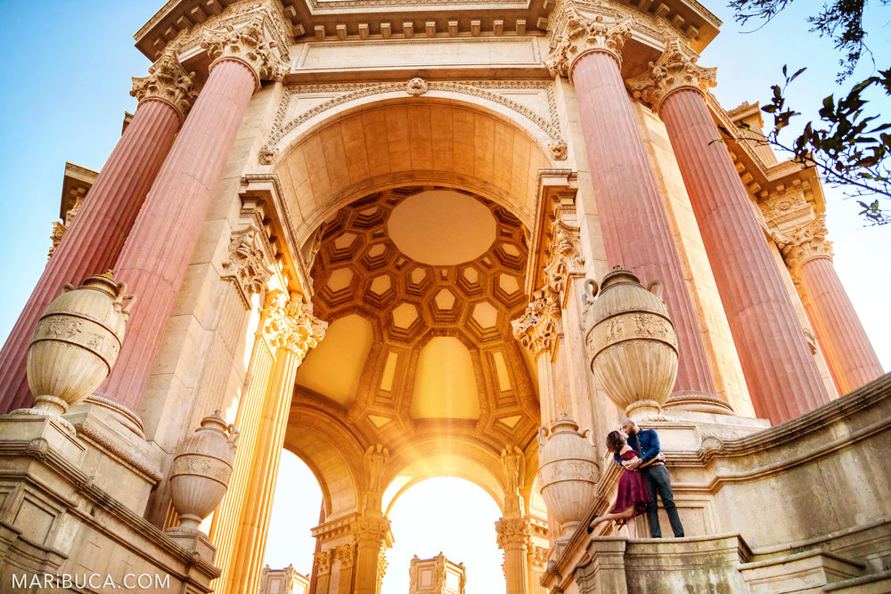 San Francisco Engagement Palace of Fine Art with fabulous couple are standing in the historical architecture stairs during orange sunset.