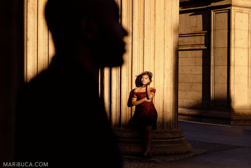 Fiance stands in the orange sunset and looks to her fiance in the San Francisco Engagement Palace of Fine Art