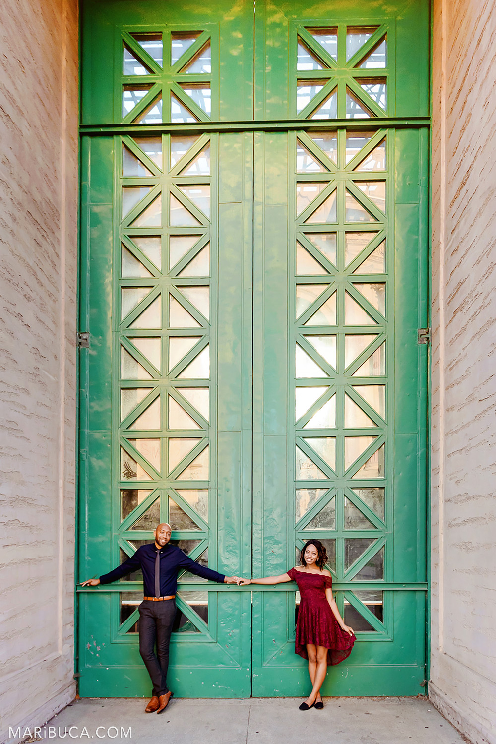 Engagement couple stand in front huge green gate in the San Francisco Engagement Palace of Fine Art