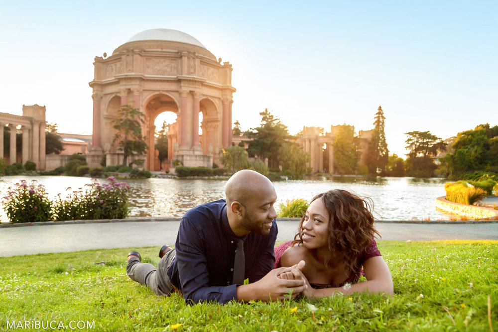 Fiance and fiancee look each other and lie in the grass in the San Francisco the Palace of Fine Art