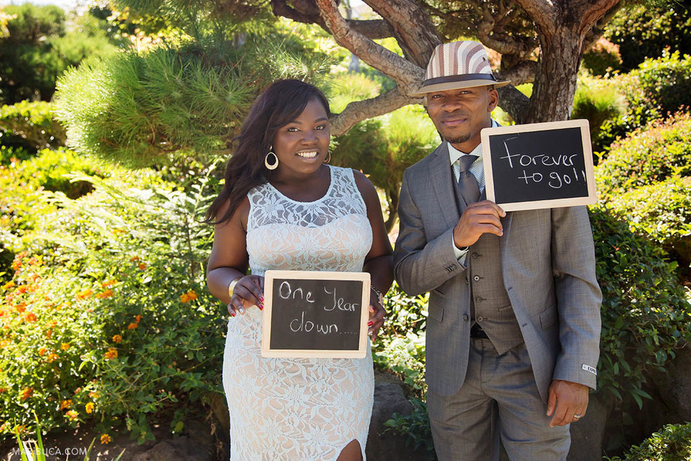 """The bride holds """"one year down"""", the groom holds """"forever to go!"""" chalkboard and they celebrate anniversary wedding in the Hayward Japanese Garden."""