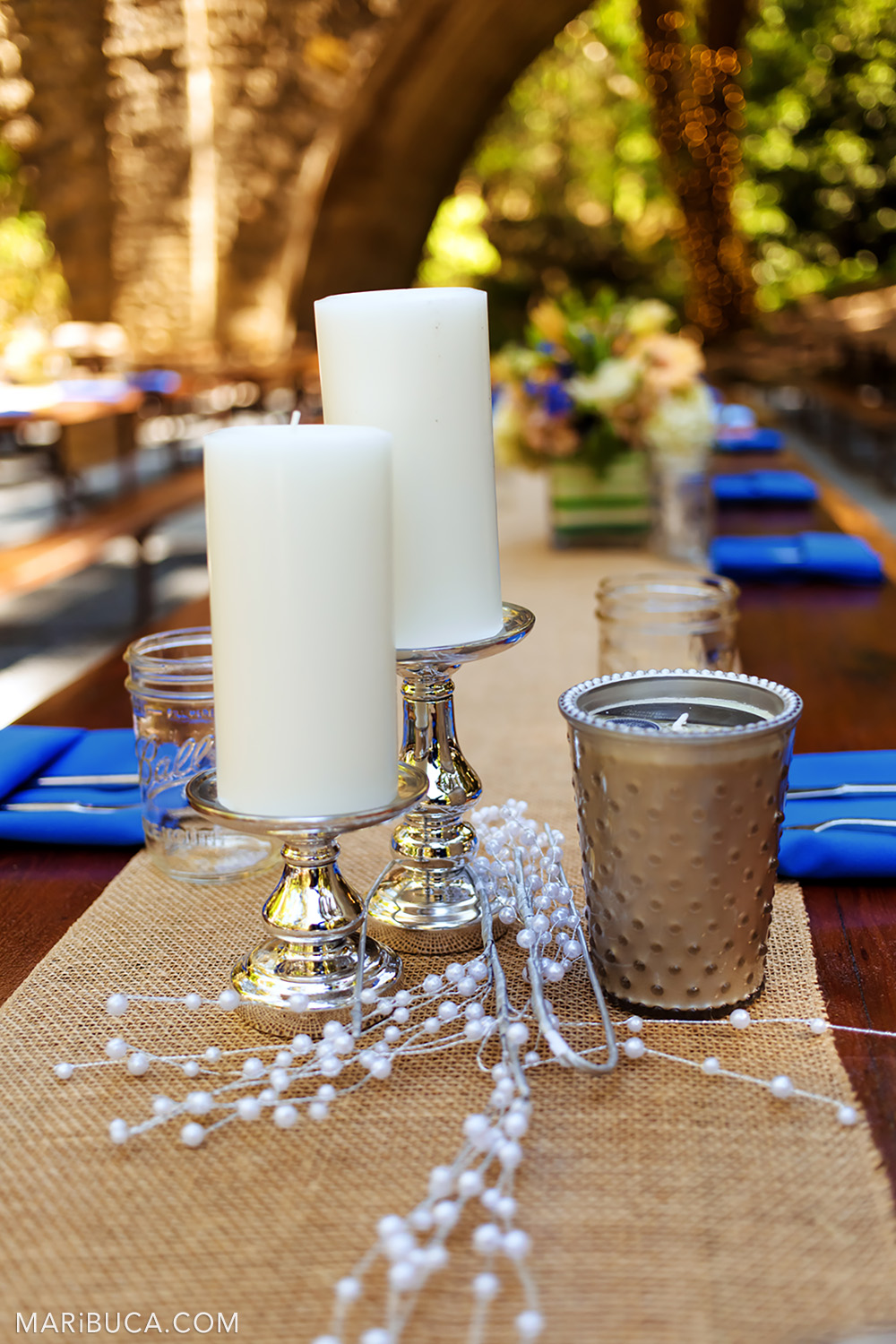 Decoration of the table with two white candles, beige tablecloth and navy blue napkins in the Saratoga Springs Venue