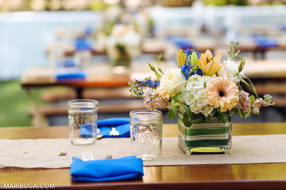 Tables decorations in the wedding: glasses, colorful flowers in the vases in the Saratoga Springs Venue