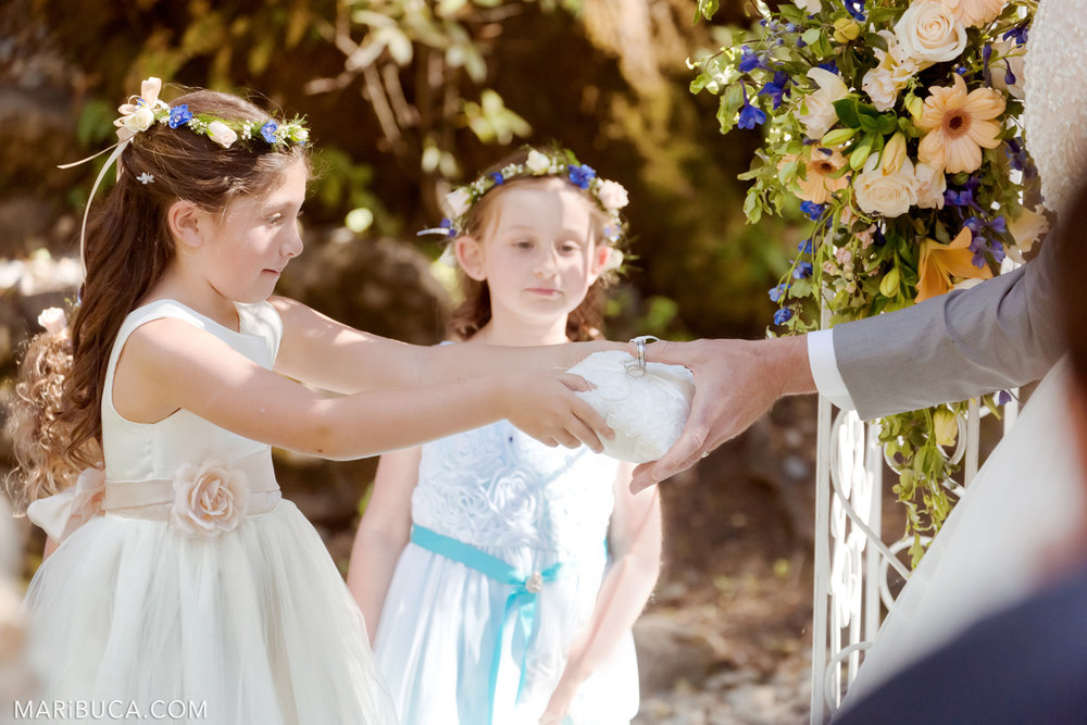 The flower girl in the white dress with light pink roses gave the rings to the groom in the Saratoga Springs Wedding.