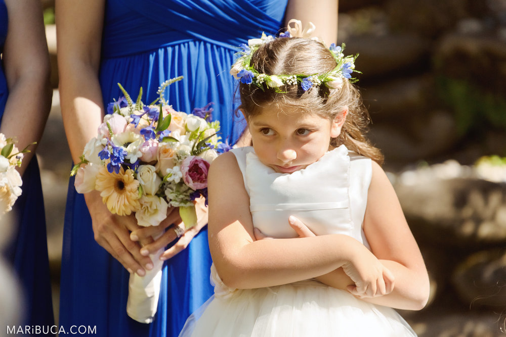 The flower girl hugs the white wedding pillow during the wedding ceremony in the in the Saratoga Springs Wedding