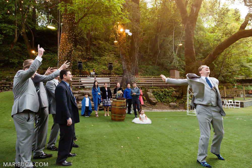 The groom tosses white garter to his friends in the Saratoga Springs Wedding