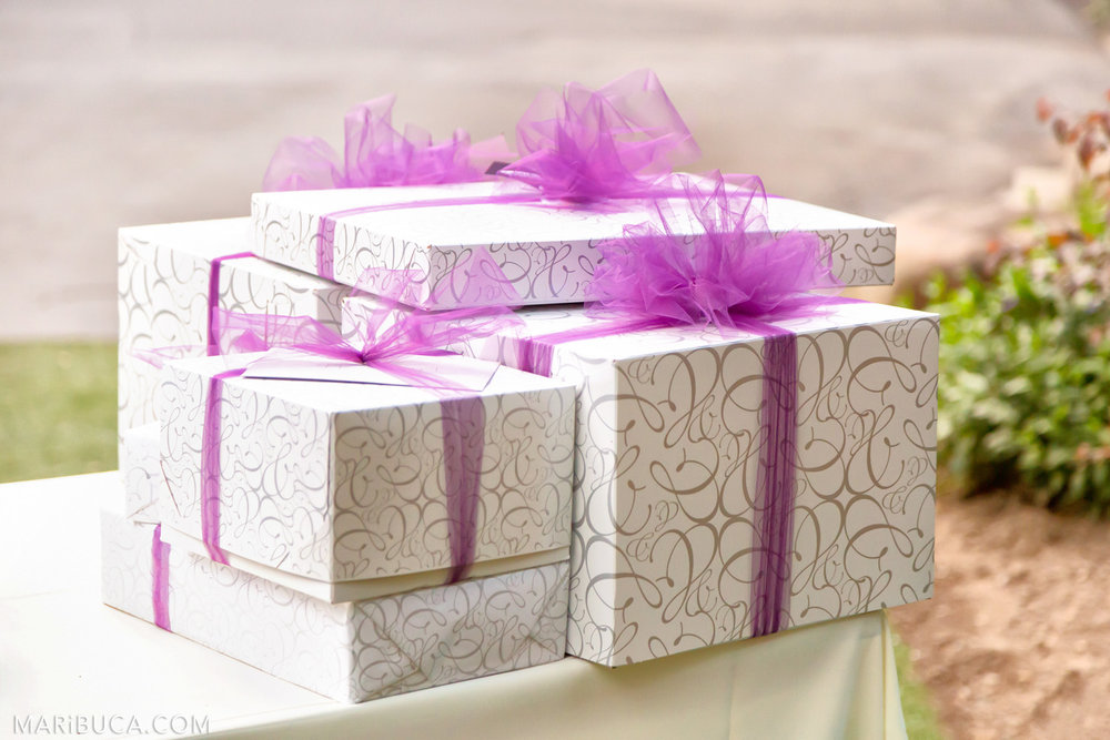 Wedding gifts: white boxes with ornament elements and purple ribbon in the Saratoga Springs Wedding