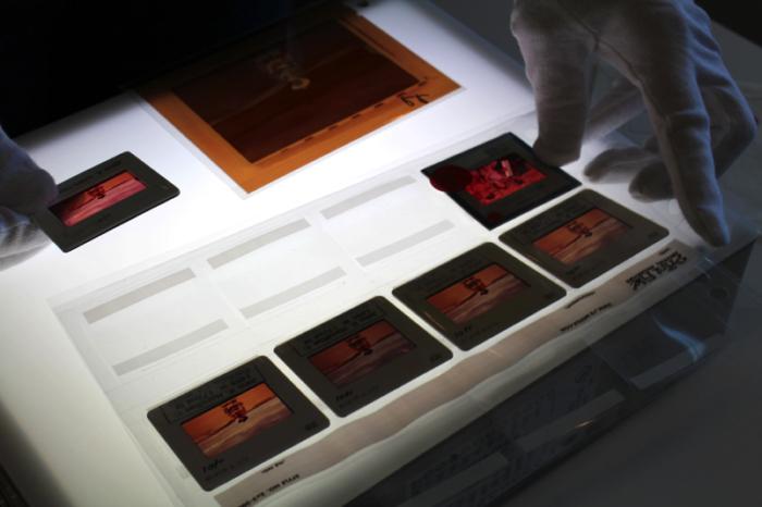 Original slides featuring John Wayne on the set of  The Searchers  (1956) are viewed using a lightbox. Photo courtesy of John Wayne Enterprises