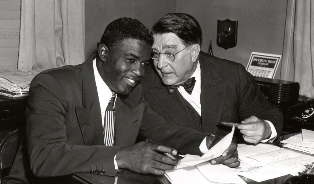 Jackie Robinson signs a contract with the Brooklyn Dodgers president Branch Rickey, 1950.  Getty Images/Transcendental Graphics / Contributor