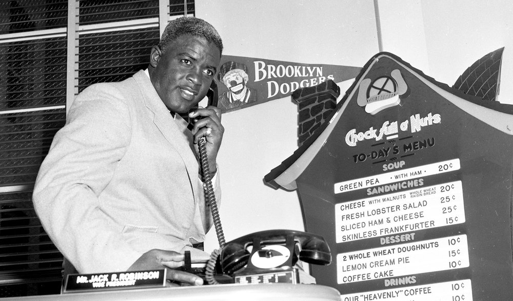 Jackie Robinson at his desk at Chock Full o'Nuts, 1957.   Getty Images/Transcendental Graphics / Contributor
