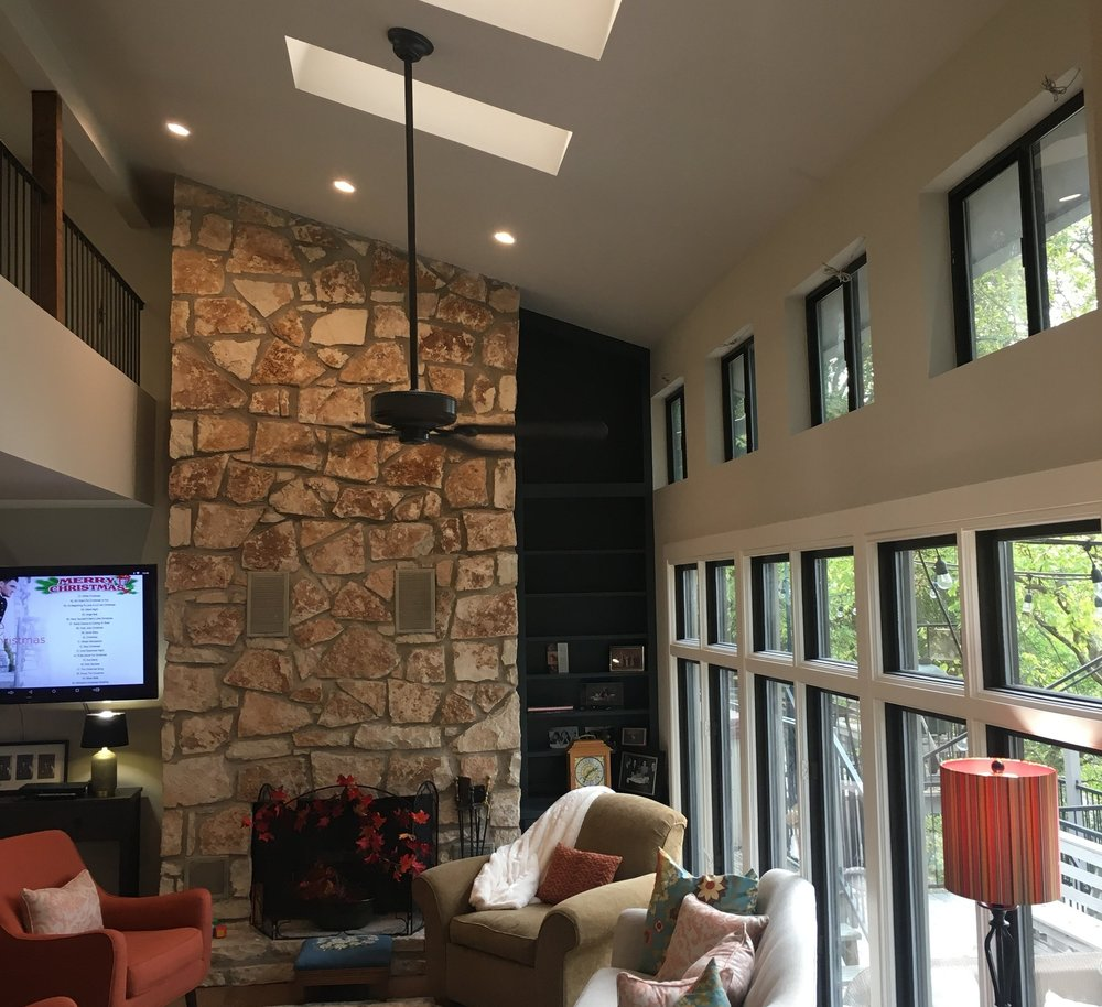 Custom built-in bookcases flanking stone fireplace in Austin, Texas.