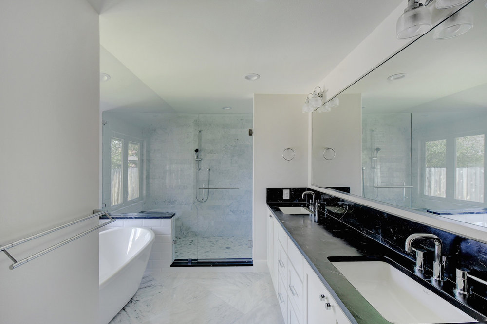 modern bathroom with freestanding tub, walk-in shower, and black countertops