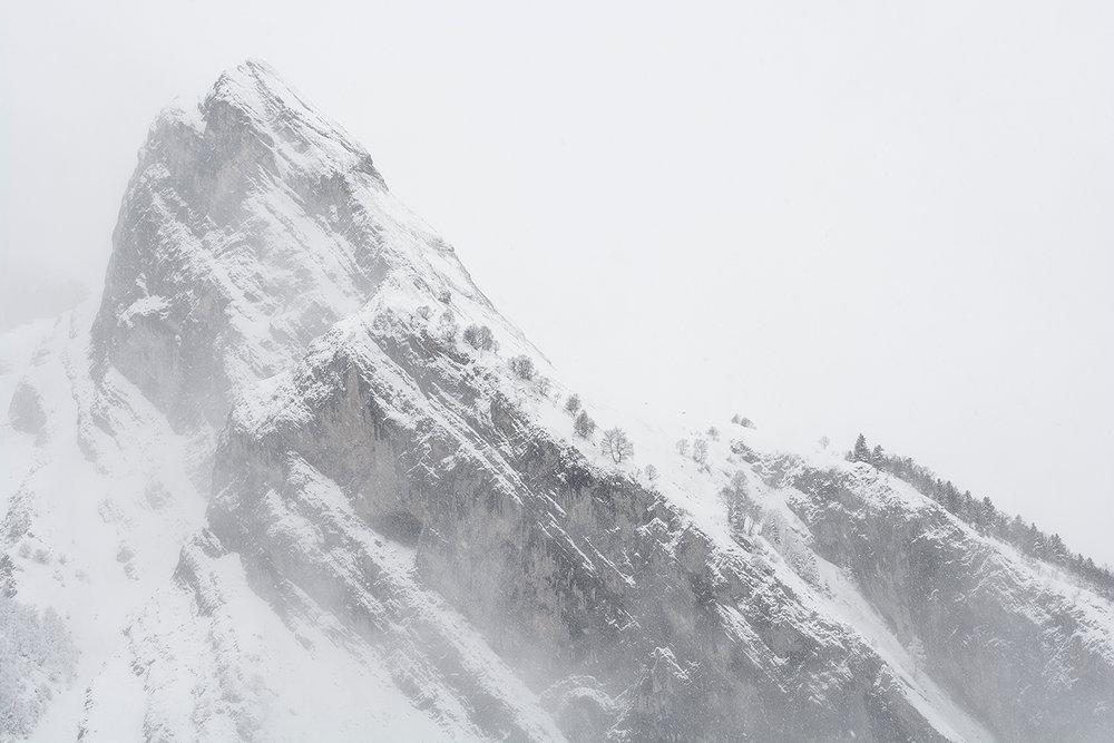 """""""Paré d'une fine pellicule blanche, le pic imposant apparaît plus majestueux encore que la veille. La météo, capricieuse, entame alors un étrange et envoûtant ballet : un épais brouillard avale le paysage, les nuages déversent une pluie de coton. Successivement, les montagnes s'effacent, pour surgir ensuite en déchirant les écharpes de brume, puis s'évanouissent à nouveau."""""""