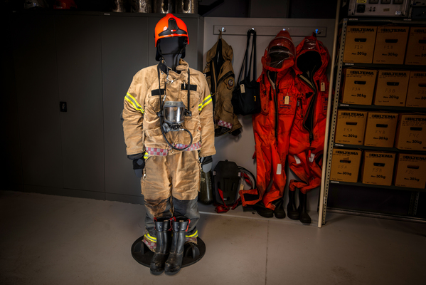 Firefighter uniform - Clothing for emergency response personnelClothing for emergency response personnel (boots are missing), including smoke diving mask. Back frame and oxygen tank on the floor. On the wall are survival suits, for use by personnel on board rescue boats.This equipment originally came from Narvik Airport Framnes. Oxygen tank and boots came from Fagernes Airport Leirin.
