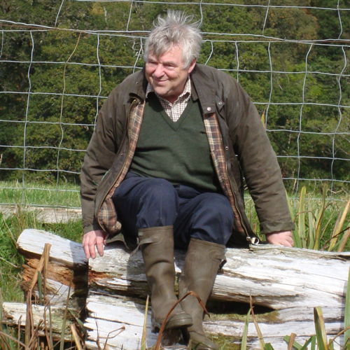 - John Fletcher is a vet specialising in deer; he also keeps a small herd of rare white red deer and also writes books. Here he is relaxing on a log in the Highlands. www.deervet.com
