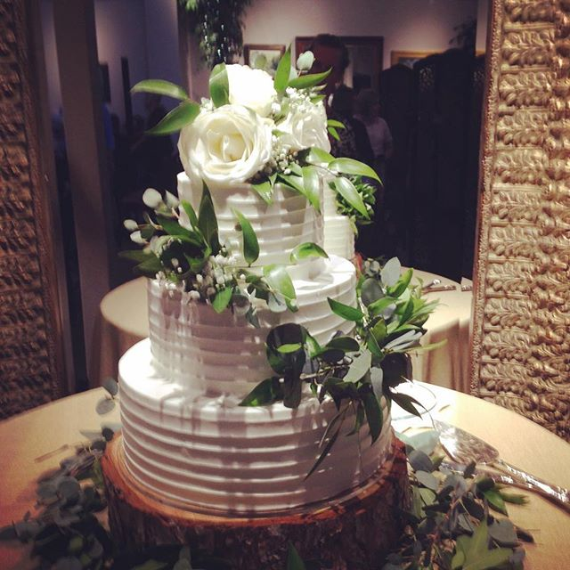 Dressing up a cake with a white flower and greenery topper and greenery tier clusters and the last touch of having loose greenery to sprinkle on the table.