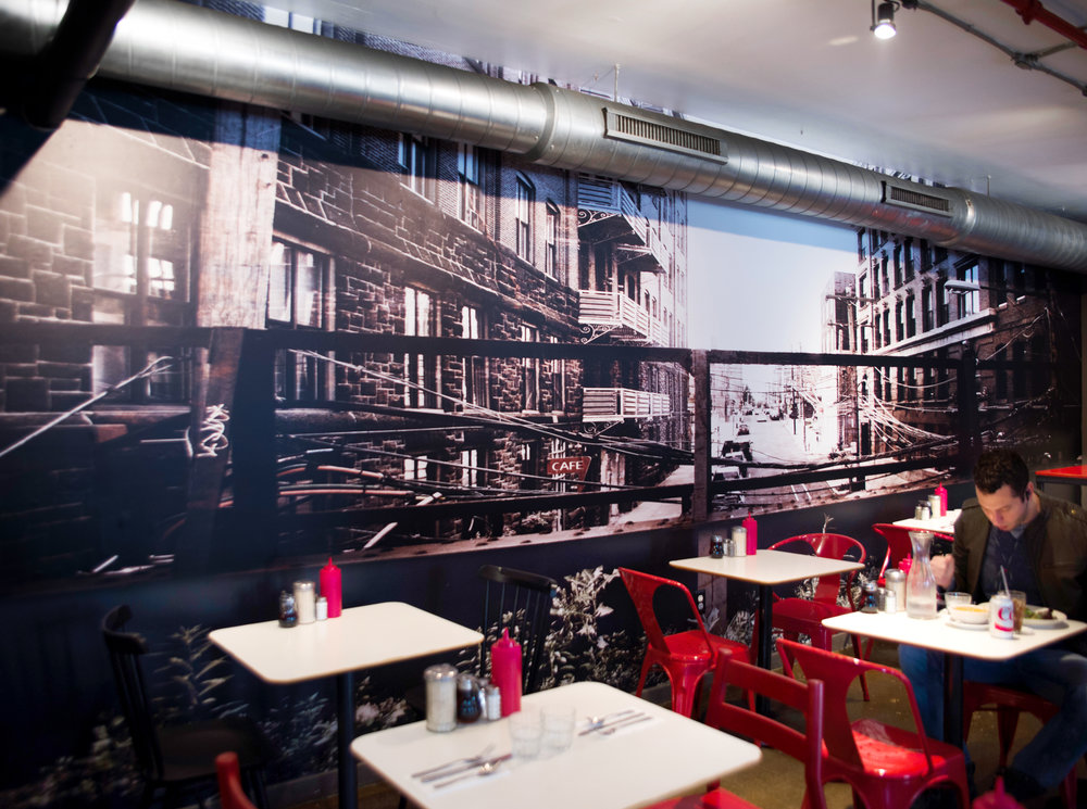 Michael Pasquarello hired Julia Blaukopf to create a custom, photo-based wall covering for the accent wall in his restaurant Cafe Lift . The goal was to highlight the surrounding area with special emphasis on The Rail Park