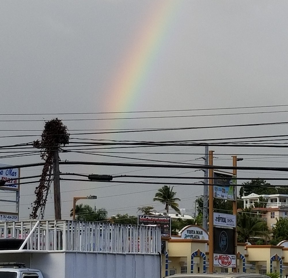 an afternoon rainbow over power lines