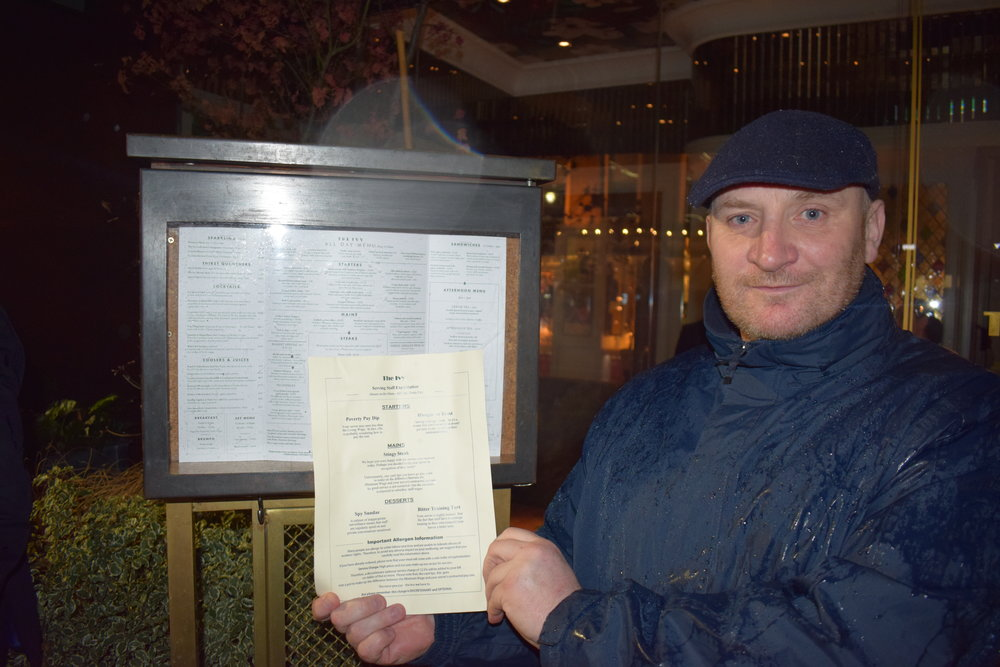 Damien Farrell holding up a mock 'menu' outside The Ivy