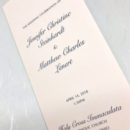 Folded wedding program on natural white with blue text