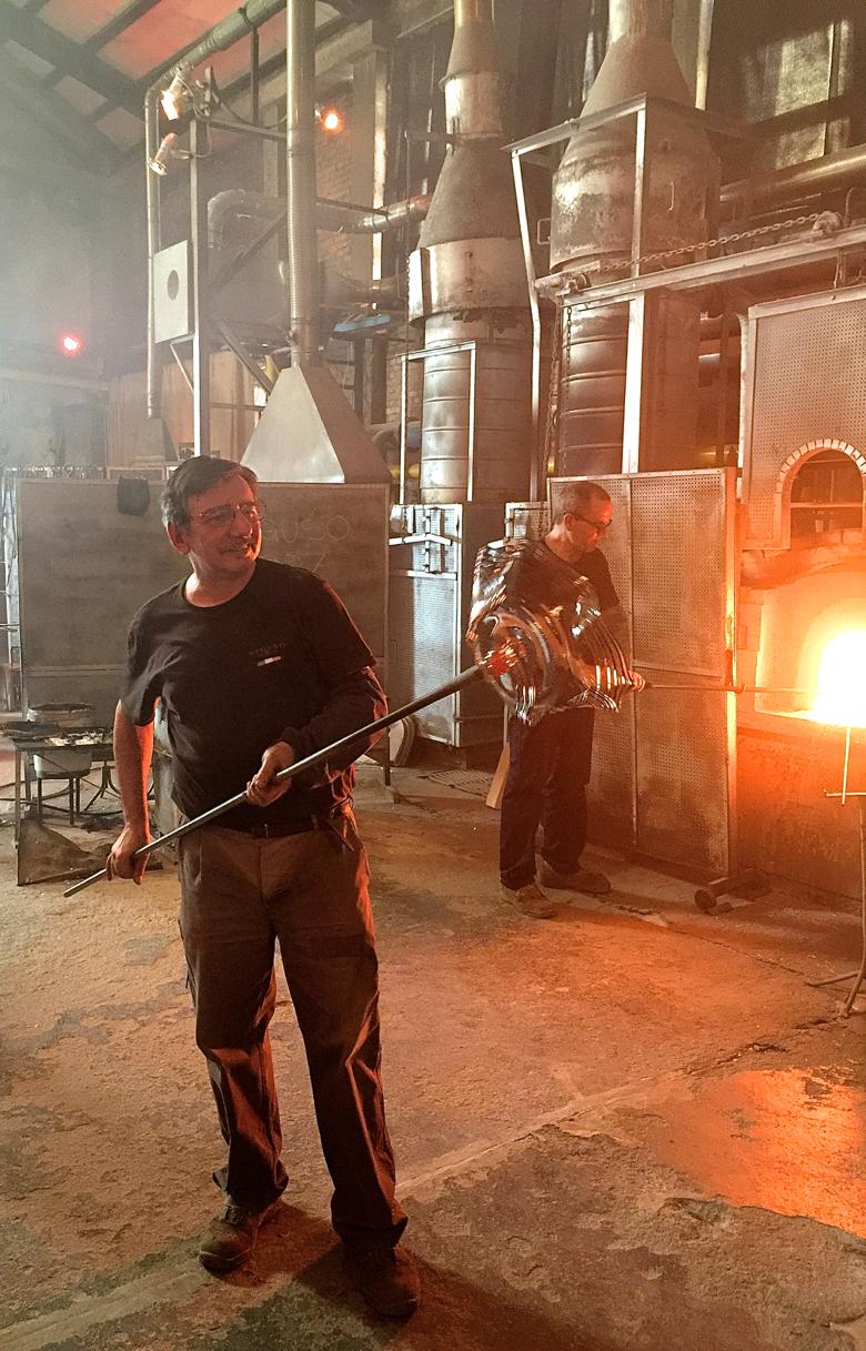 A Seguso glass artisan crafting a Murano vase