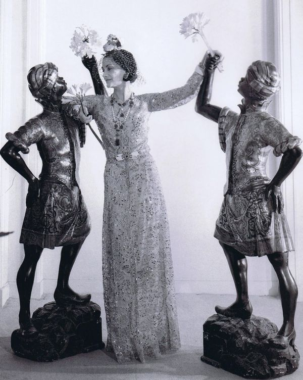 Coco Chanel with a pair of Blackamoor scuplture