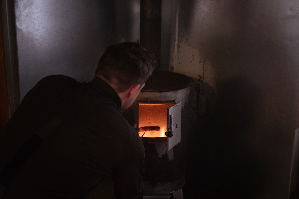 Tommi a 33 years old border guard officer heats up a sausage in the stove of the cottage. Breaks during patrols are very important. Especially during winter time, the body consumes a lot of energies to stay warm and it's important for the Border Guards to always be in optimal working conditions.