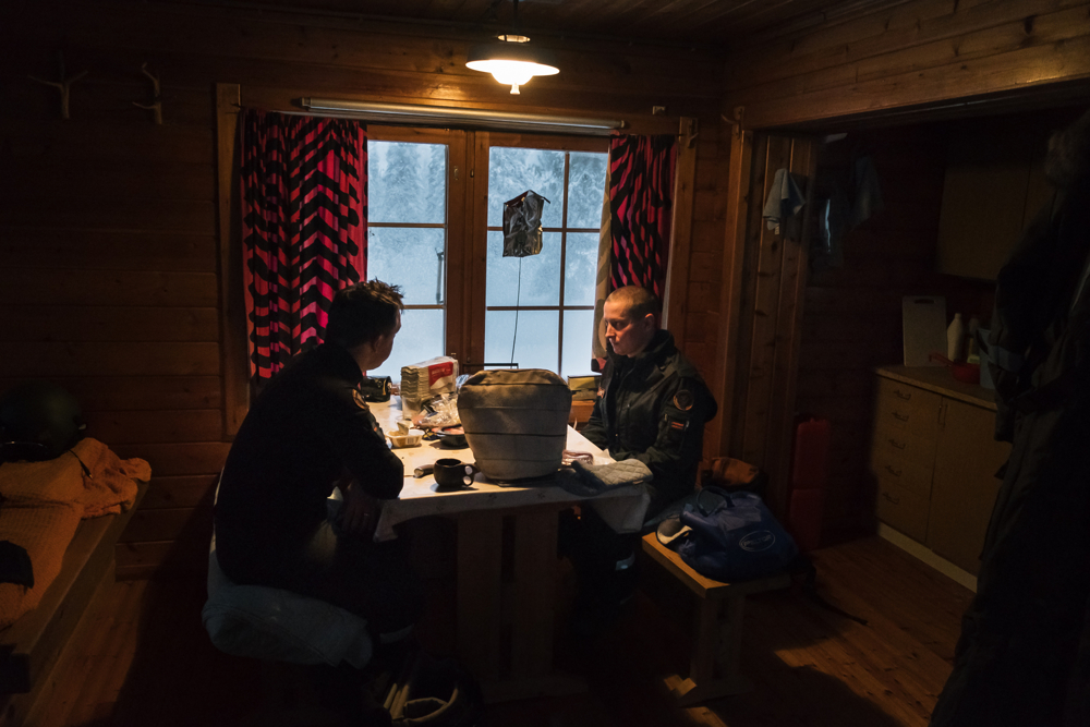 After starting the wooden stove Tommi and Mika eat some food and drink some coffee before continuing with the patrol. Visiting the cottages continuously is important to keep them in operative conditions and to memorise their location in the forest.