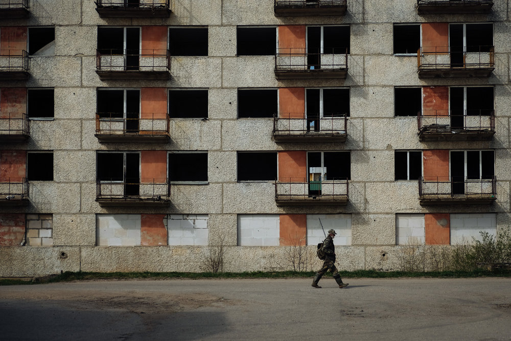 Jekabpils - Zemgale. A fisherman walks in front of an abandoned building in a neighbourhood of the city. The presence of unfinished and abandoned buildings is very high around the city.