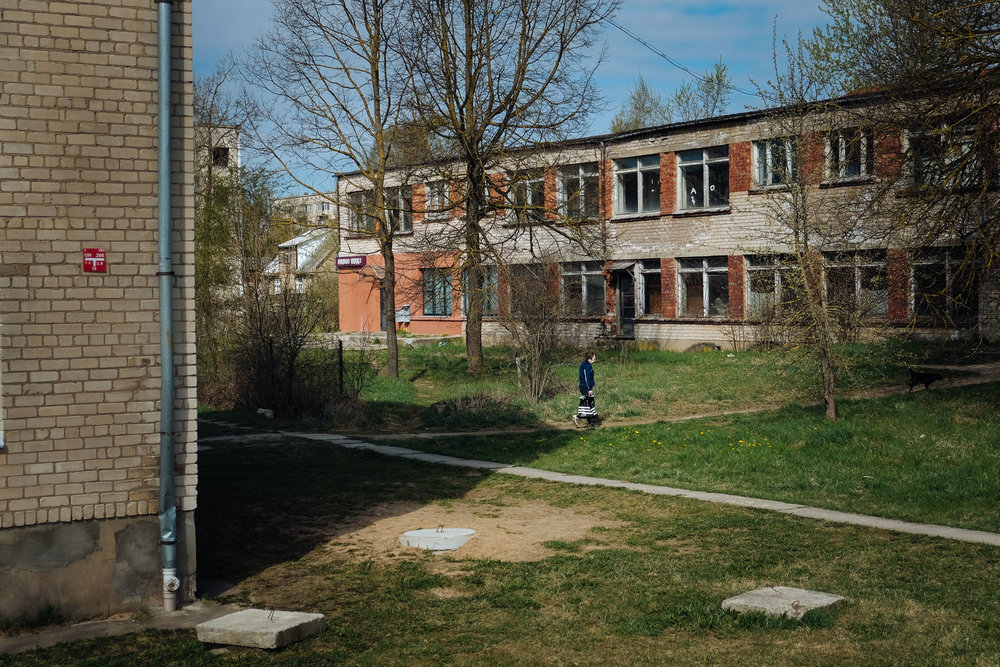 Jekabpils - Zemgale. Just outside the city center a woman is seen walking among block of flats partially abandoned.
