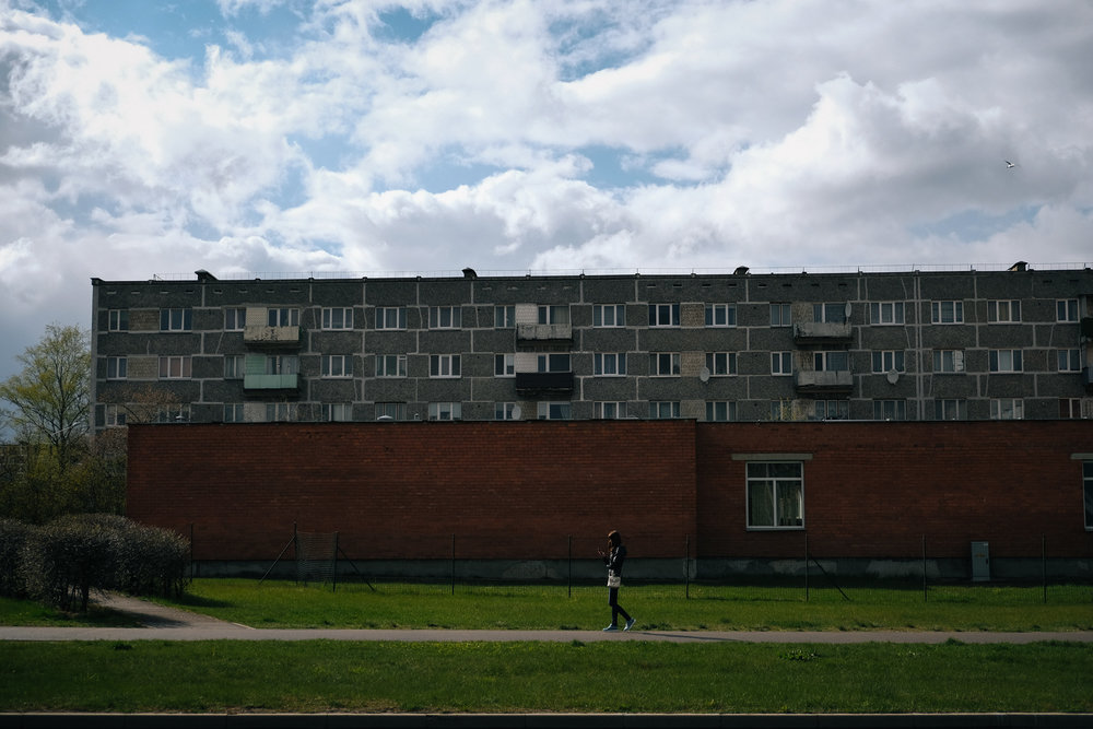 Daugavpils - Latgale. A young girls is seen walsking by a block of flats built in the USSR occupation time. Latgale is the second largest city of Latvia and has been suffering very high rates of emigration. In the last 15 years almost 30% of the population has emigrated abroad or to Riga.