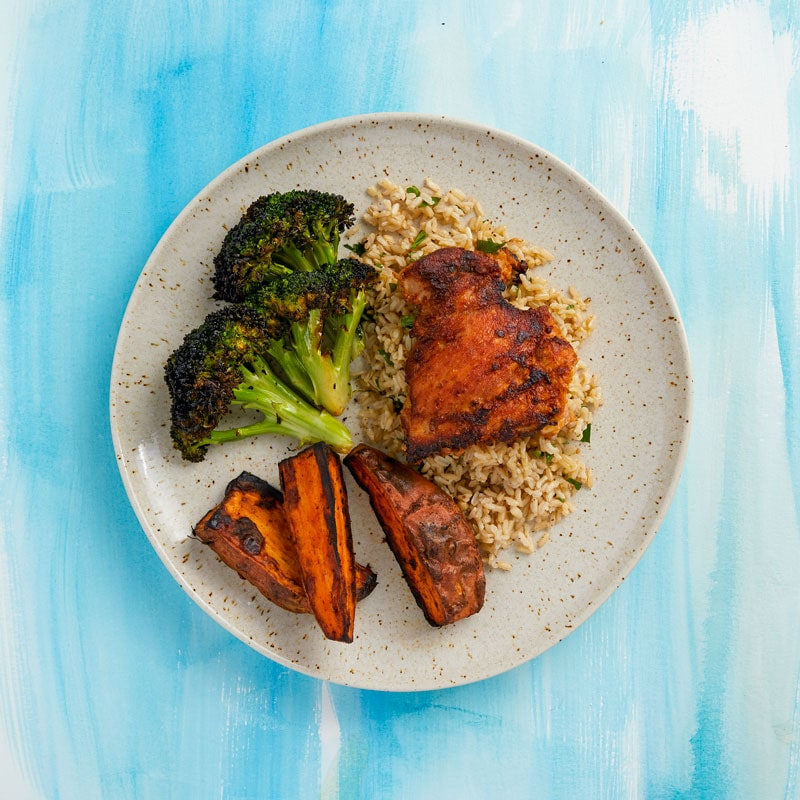 Classic Grilled Chicken  Boneless chicken thigh, brown rice, roasted sweet potato, charred broccoli.