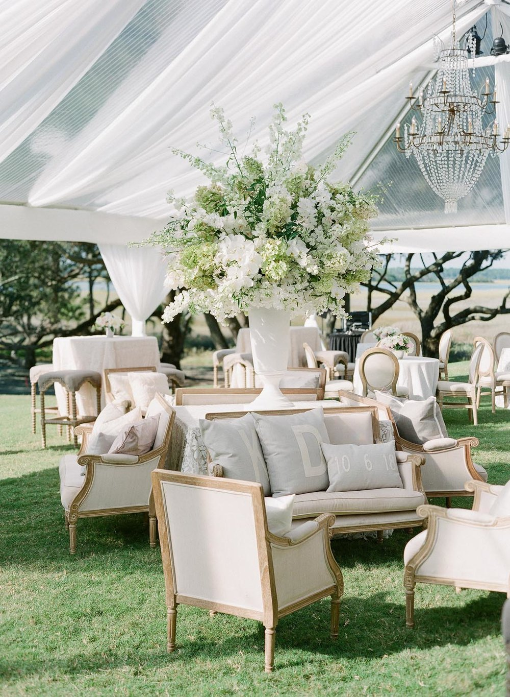 Strolling oyster shuckers, a champagne and bourbon bar as well as a clear top tent with the dreamiest draping, floral and lounge. Wedding planning and design by A Charleston Bride.