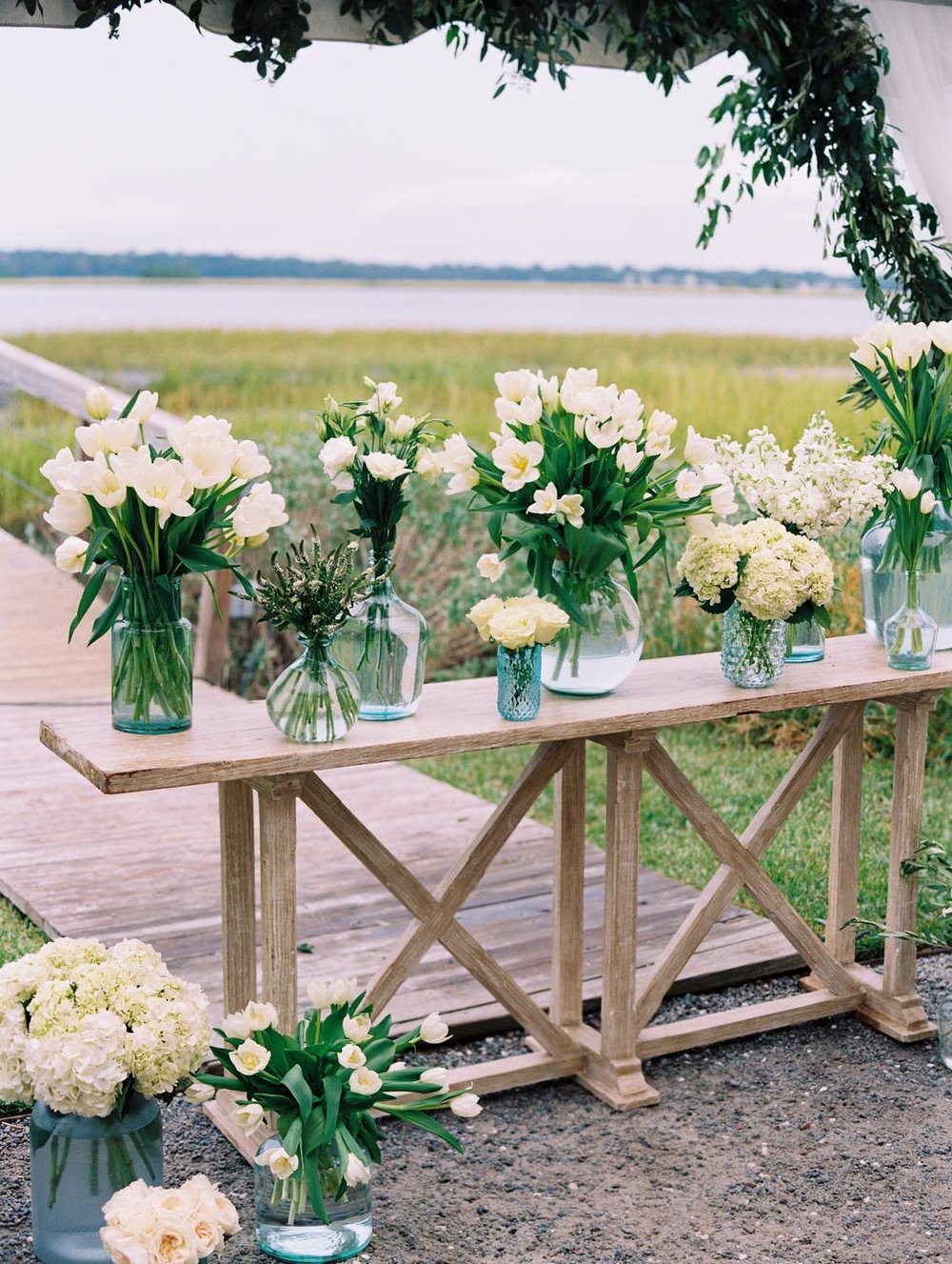 We complimented crisp green and white florals with wood and hints of blue and green to set the tone for the evening. Wedding planning and design by A Charleston Bride.
