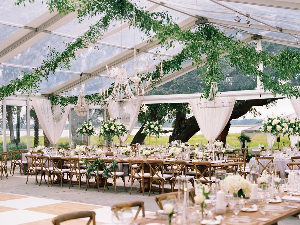 From the clear top tent dripping in greenery to the clean lines of fabric hugging the perimeter of the space, this outdoor wedding was the epitome of southern sophistication. Wedding planning and design by A Charleston Bride.