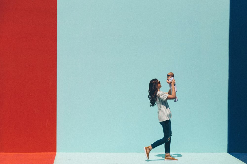 Red, light blue and dark blue stripe wall. Mother holding baby walking past the wall.