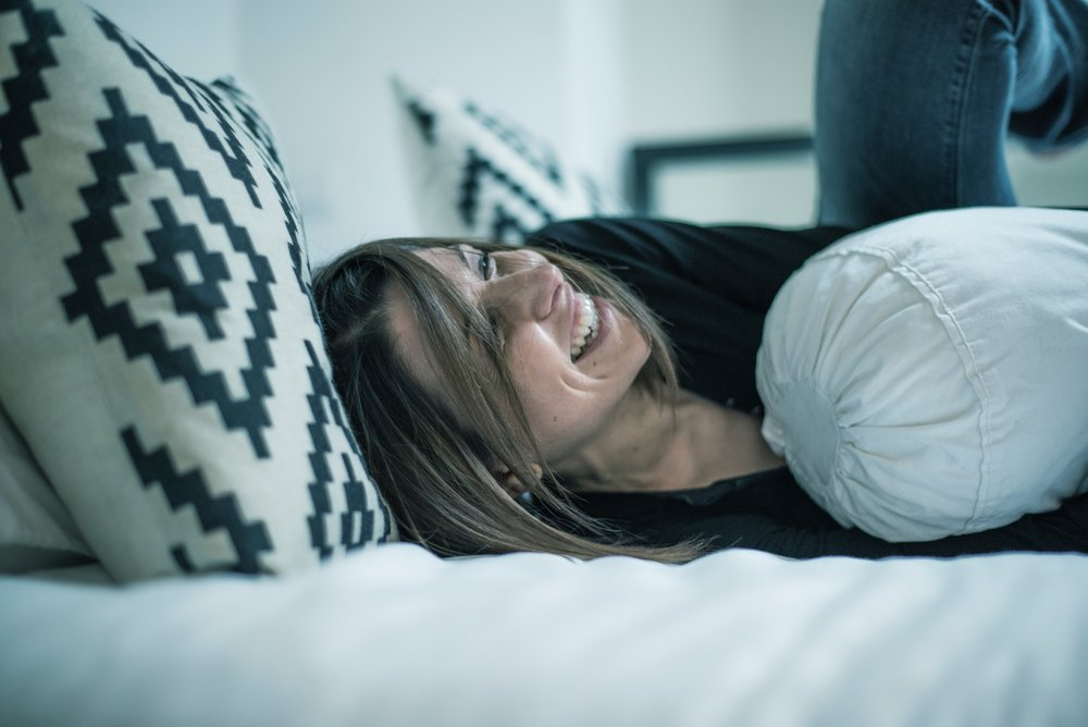Woman smiling as she falls on a bed.