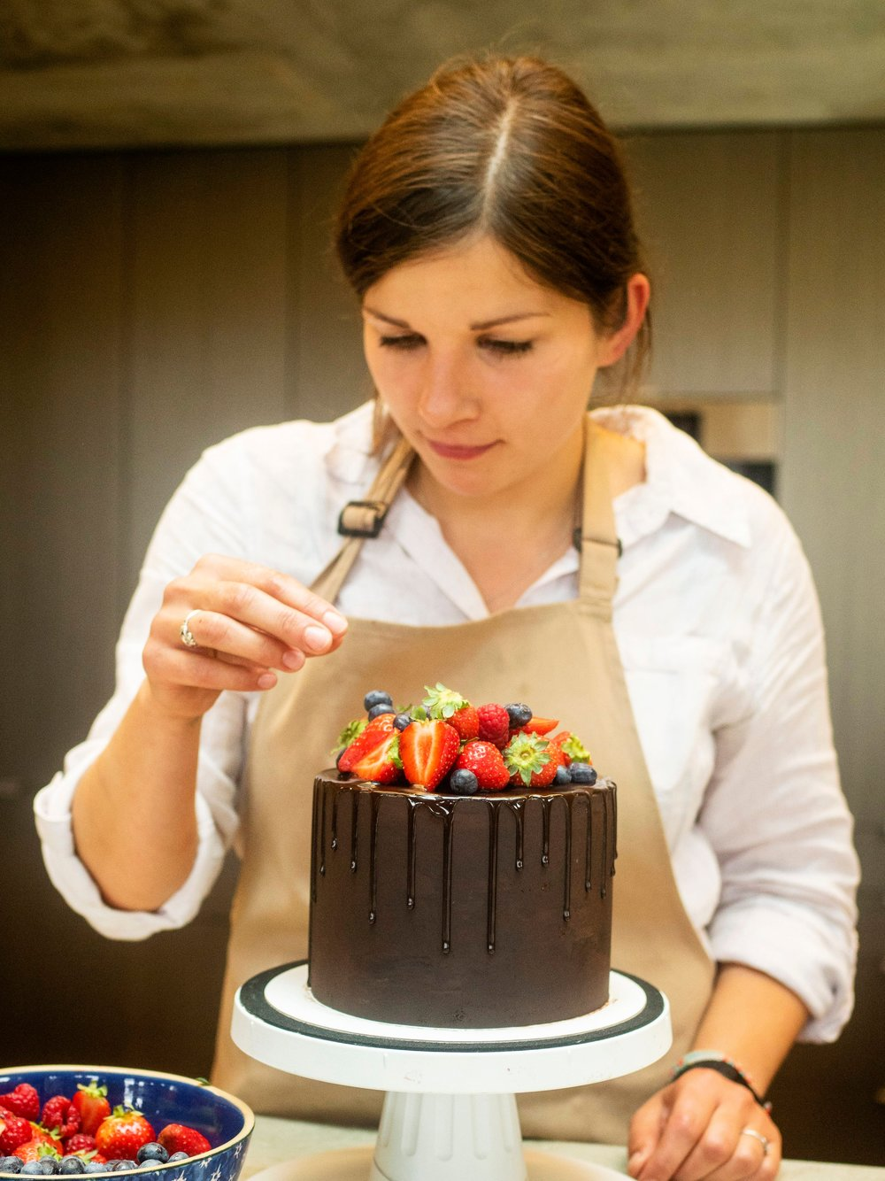 Gabi, decorating a chocolate drizzle cake with forest fruits.