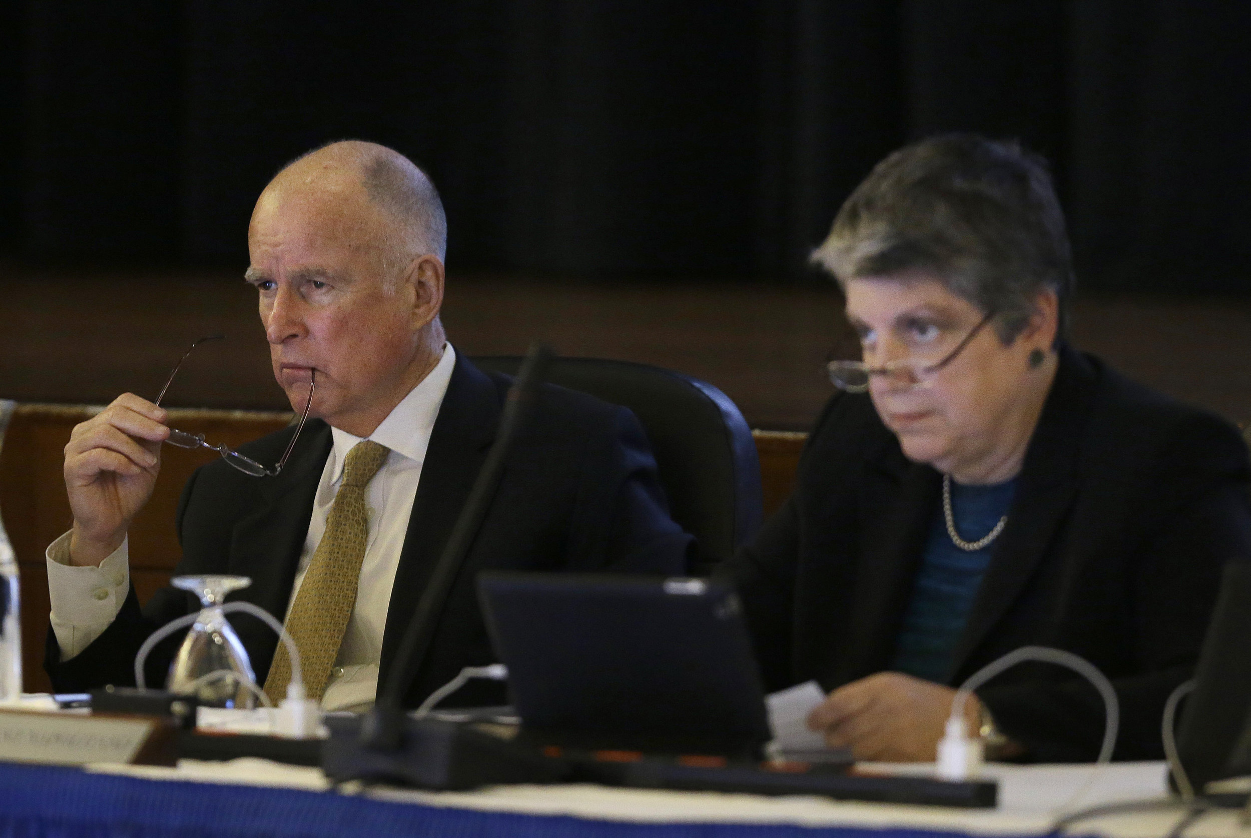 In this file photo from Wednesday, Jan. 22, 2014, California Gov. Jerry Brown, left, and University of California president Janet Napolitano listen to speakers during a UC Board of Regents meeting in San Francisco. Legislative analysts in Sacramento are releasing their review of Brown's proposed higher education budget. The recommendations may figure into the ongoing negotiations over the University of California's finances, which so far have had lawmakers and the governor taking a dim view of UC President Janet Napolitano's plan to expand undergraduate enrollment by raising tuition. (AP Photo/Jeff Chiu)