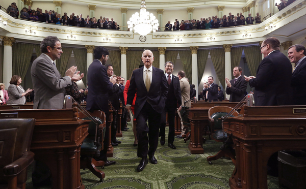Gov. Jerry Brown receives applause from lawmakers as he walks to podium of the Assembly chambers to deliver his State of the State address at the Capitol in Sacramento, Calif., Wednesday, Jan. 22, 2014. Brown delivered a dual message in his annual address to the Legislature, that a California resurgence is well underway but is threatened by economic and environmental uncertainties.(AP Photo/Rich Pedroncelli, pool)