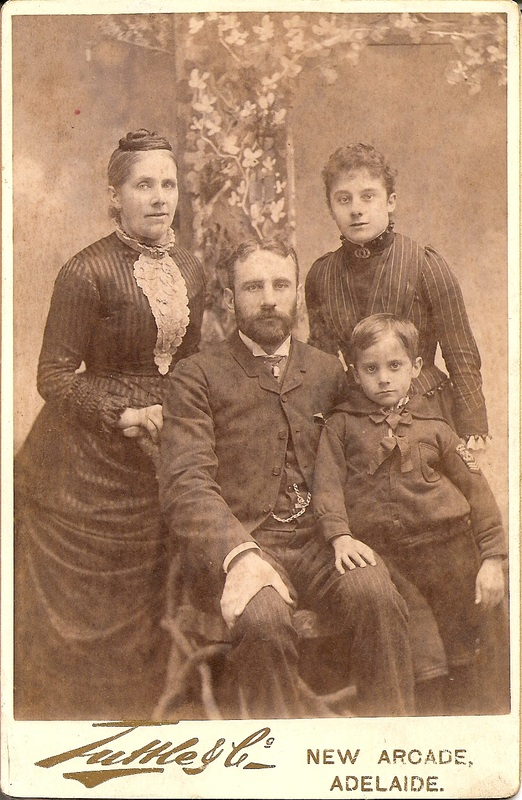 """The Walter family in Adelaide in 1888.  While the caption on the back of this photograph claims that the individuals pictured were E Walter, A Grainger, L.G. Walter and W.G. Walter (that is, Elizabeth, her children, Lilian Grace and William Gilbert, and an """"A Grainger"""" - perhaps her brother Alfred), the photograph also provides specific information about the family's arrival in Australia and, in another handwriting, notes that the man is """"Marie's grandfather"""" - that is, John Spencer Walter. Since the Walters travelled to Australia as a family and, logically, would be photographed as a family, it seems more likely that this photograph depicts: Elizabeth, John and their two children."""
