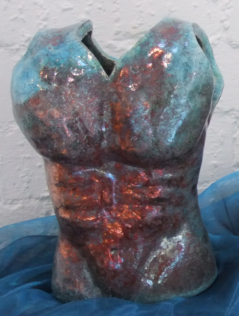 Turquoise Glaze. The red lustres are created during the firing.