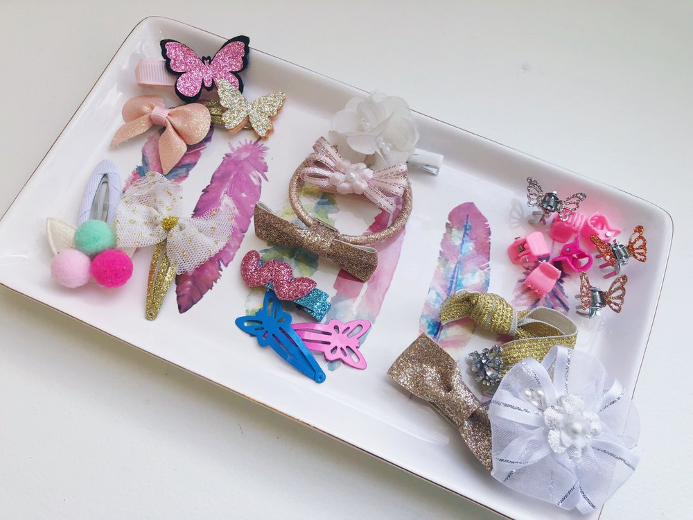 trinket trays - These little trays are a great way to keep smaller items together, like rings and keys. There are so many beautiful trays- from mirrored to gold plated, to fun designs such as flamingos and lamas. This feathered theme tray displays my daughters favourtie hair accessories.